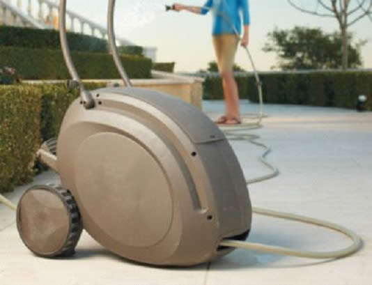 Gray color retractable hose reel with wheels is used by a young woman